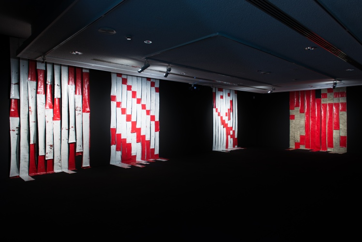 Installed at Artspace Sydney in late  2013, the work Blood on Silk: As per instructions I was exhibited in  the exhibition, Notes on the Works a survey exhibition by Ian Milliss.  As part of Milliss' open ended  practice, Ian had given instructions to other artists for the production of artworks, referencing works  he made in the early 1970s. These instructions were  - use strips of fabric 200 to 250mm wide each painted a single colour and then nail to the wall as you want The three later works Blood on Silk: As per Instructions 2,3 and 4 were made in 2014 again referencing the code  of the barber's pole and its subsequent distortion or mutation.  The code utilised in the first of this series is the pattern made by eight drops of blood falling from one metre.   photo credit Alex Wisser